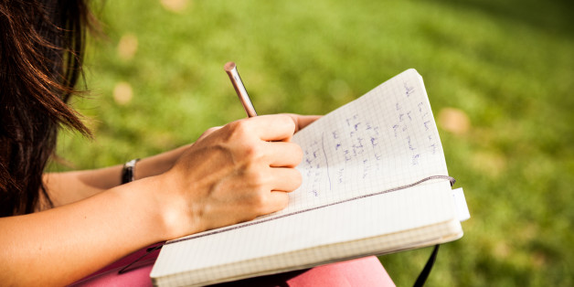 Young woman writing on diary while chilling at the park.