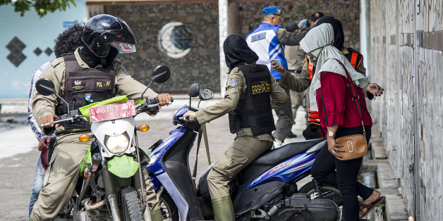 Indonesian officers (L) from the city administration police detain unmarried couples (R) after a raid at a hotel in Surabaya on February 14, 2018.Valentine's Day was banned in some Indonesian cities on February 14 as police rounded up amorous couples, giving the official kiss-off to a tradition that critics say doesn't deserve any love in the Muslim-majority nation. / AFP PHOTO / JUNI KRISWANTO        (Photo credit should read JUNI KRISWANTO/AFP/Getty Images)