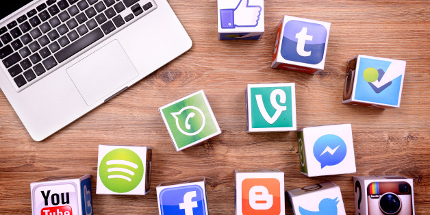 Ä°stanbul, Turkey - January 16, 2016: Paper cubes with Popular social media services icons, including Facebook, Instagram, Youtube, Twitter and a Macbook Pro laptop computer on a wooden desk.
