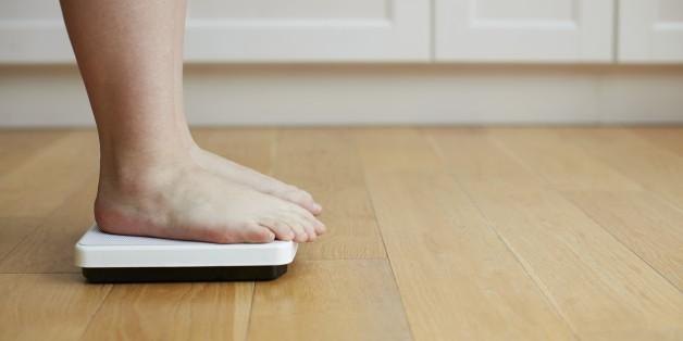 Woman standing on weighing scales.