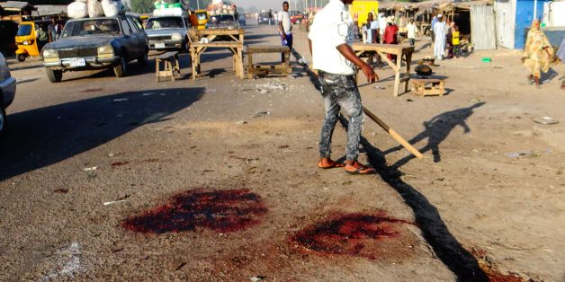 A man stands with his back to the blood stained scene of three suicide bomb blasts that left 13 people dead in Maiduguri, northeast Nigeria, on October 23, 2017.Three female suicide bombers killed 13 people and wounded 16 in the northeastern city of Maiduguri on ctober 22, 2017, security sources said.The first bomber detonated her explosive belt in front of a small restaurant in the capital of Borno state 'when people were buying their dinner,' a military source said on condition of anonymity. T