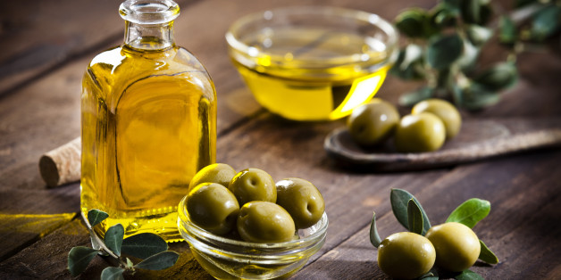 Horizontal shot of an olive oil bottle and a little glass bowl filled with green olives on rustic wood table. Two olives with leaves are at the bottom-right while a bowl filled with olive oil is out of focus at background beside olive tree branch. Predominant colors are gold, green and brown. DSRL studio photo taken with Canon EOS 5D Mk II and Canon EF 70-200mm f/2.8L IS II USM Telephoto Zoom Lens