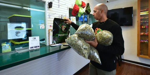 Cannabis entrepreneur Virgil Grant carries bags of medical marijuana at a dispensary he runs in Los Angeles, California on February 8, 2018.Virgil Grant is riding the high on California's cannabis legalization, with a burgeoning empire that already comprises three dispensaries, two plantations and a line of apparel. His success has come as some compensation for the six years lost inside the federal prison system for dealing the drug. / AFP PHOTO / Frederic J. BROWN / TO GO WITH AFP STORY by Vero