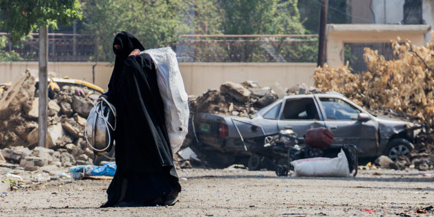 A woman is fleeing from a neighbourhood in western Mosul where fights between the federal Police and ISIS are taking part (Photo by Sebastian Backhaus/NurPhoto via Getty Images)