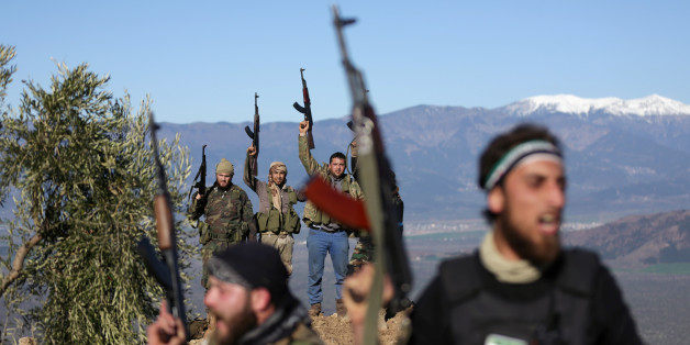 Turkish-backed Free Syrian Army fighters react as they hold their weapons near the city of Afrin, Syria February 19, 2018. REUTERS/Khalil Ashawi