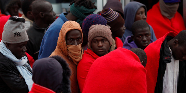 Migrants, part of a group intercepted aboard a dinghy off the coast in the Mediterranean Sea, stand after arriving on a rescue boat at the port of Malaga, Spain January 13, 2018. REUTERS/Jon Nazca