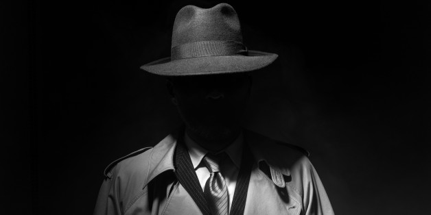 Man posing in the dark with a fedora hat and a trench coat, 1950s noir film style character