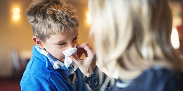 Mother blowing nose of her sick son.