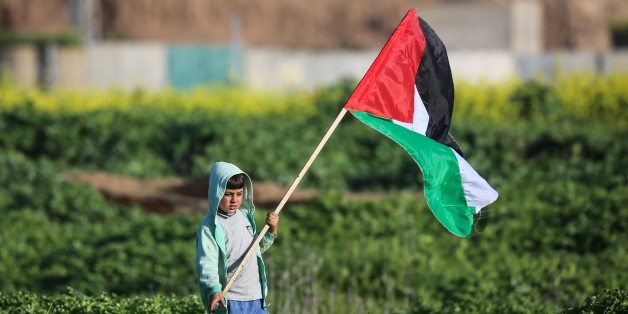 GAZA CITY, GAZA - FEBRUARY 23: A Palestinian child holds a Palestinian flag during a protest against U.S. President Donald Trumps announcement to recognize Jerusalem as the capital of Israel, in Shuja'iyya neighborhood of Gaza City, Gaza on February 23, 2018. (Photo by Ali Jadallah/Anadolu Agency/Getty Images)