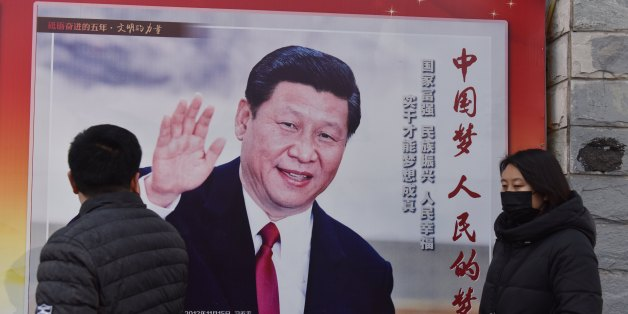 People walk past a poster of Chinese President Xi Jinping beside a street in Beijing on February 26, 2018.Xi Jinping's tightening grip on China had already earned the leader comparisons to Mao Zedong, but they came into even sharper focus after the party paved the way for him to assume the presidency indefinitely. / AFP PHOTO / GREG BAKER        (Photo credit should read GREG BAKER/AFP/Getty Images)