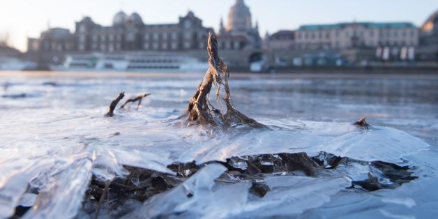 The frozen shore of the Elbe is pictured at sunrise in front of a backdrop of the old town of Dresden, Germany, on February 26, 2018.A wintry blast of freezing temperatures sweeps across Europe, with a biting wind from Siberia. The 'Beast from the East', as the phenomenon has been dubbed by the British media, is expected to bring cold air from Russia over the next few days that will make it feel even chillier than thermometers indicate. / AFP PHOTO / dpa / Sebastian Kahnert / Germany OUT