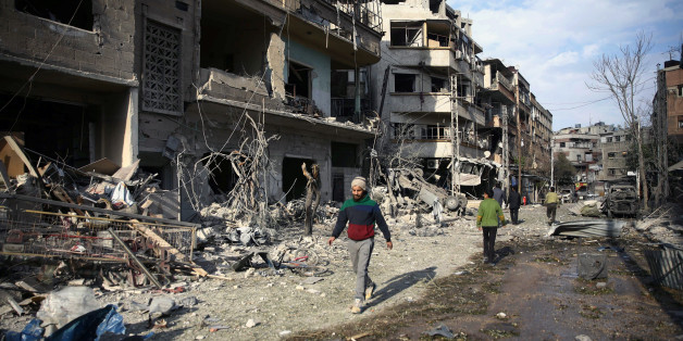 People walk through the damage, after an air raid in the besieged town of Douma, Eastern Ghouta, Damascus, Syria February 23, 2018. REUTERS/Bassam Khabieh