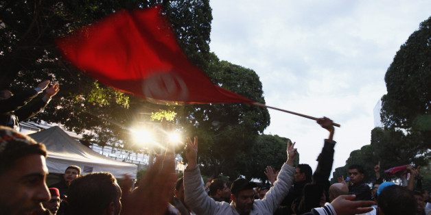 People wave a Tunisian national flag as they dance on Avenue Habib Bourguiba celebrating the second anniversary of the Tunisian revolution in Tunis January 12, 2013.  REUTERS/Anis Mili (TUNISIA - - Tags: POLITICS CIVIL UNREST ANNIVERSARY)