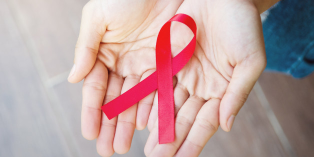 Female hands holding red ribbon HIV, AIDS awareness ribbon, healthcare and medicine concept. retro effect.