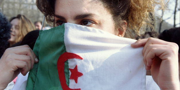 An Algerian girl hides her face in behind an Algerian flag during a demonstration campaigning for women rights in Algeria in Paris March 9. Hundreds of people demonstrated in central Paris the day after international women's day.FRANCE ALGERIA