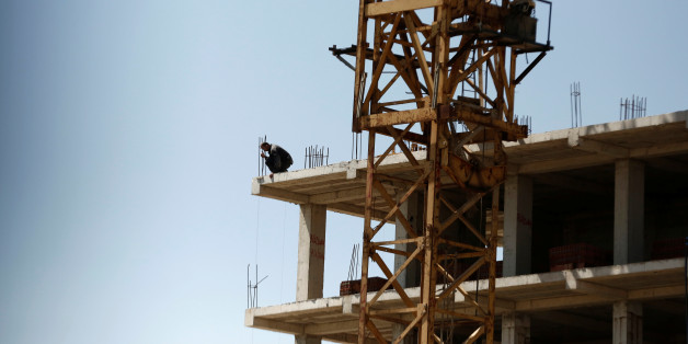 A worker looks down from the top of a new apartment building being built at a construction site in Algiers, Algeria May 3, 2016. REUTERS/Zohra Bensemra