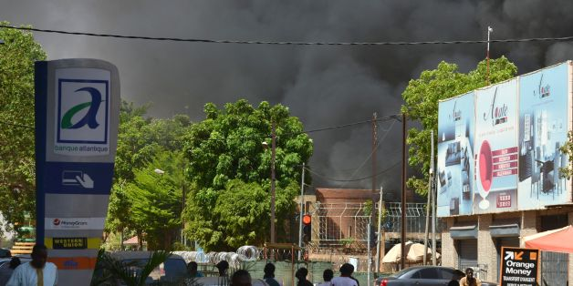 People watch as black smoke rises as the capital of Burkina Faso came under multiple attacks on March 2, 2018, targeting the French embassy, the French cultural centre and the country's military headquarters.Witnesses said five armed men got out of a car and opened fire on passersby before heading towards the embassy, in the centre of the city. Other witnesses said there was an explosion near the headquarters of the Burkinabe armed forces and the French cultural centre, which are located about a