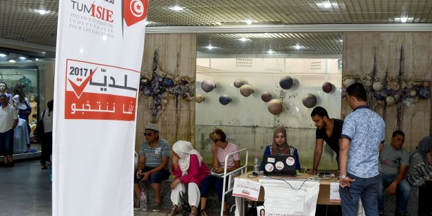 A picture taken on August 4, 2017 shows employees of the Tunisian ISIE elections body sitting at an outreach booth at a shopping mall in the capital Tunis, in a bid to encourage citizens to register to vote in the upcoming municipal elections, due in December 2017. / AFP PHOTO / FETHI BELAID        (Photo credit should read FETHI BELAID/AFP/Getty Images)