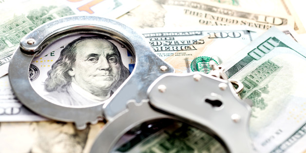Handcuffs lying on american dollars, financial crime concept.