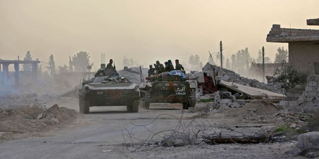 Syrian government forces drive military vehicles in al-Shifoniya as they advance in the rebel-held Eastern Ghouta area on March 4, 2018.Syria's regime seized control of over a quarter of rebel-held Eastern Ghouta on the edge of Damascus after two weeks of devastating bombardment, sending hundreds of civilians into flight, a monitor said Sunday. / AFP PHOTO / STRINGER        (Photo credit should read STRINGER/AFP/Getty Images)