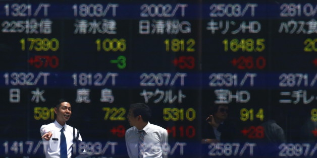 Men are refelcted in a screen displaying market indices outside a brokerage in Tokyo, Japan April 19, 2016. Japan's Nikkei share average soared on Tuesday morning, as a weak yen and a bounce in oil prices helped the market erase a sharp drop from the previous day.   REUTERS/Thomas Peter