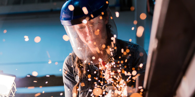 Female welder working in her workshop using an angle grinder. Los Angeles, America. October 2016