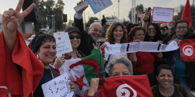 Women wave flags of Tunisia and Algeria, while raising placards and making victory signs, during a march held in Tunis, Tunisia to call for equal inheritance rights and gender equality, on March 10, 2018. (Photo by Chedly Ben Ibrahim/NurPhoto via Getty Images)