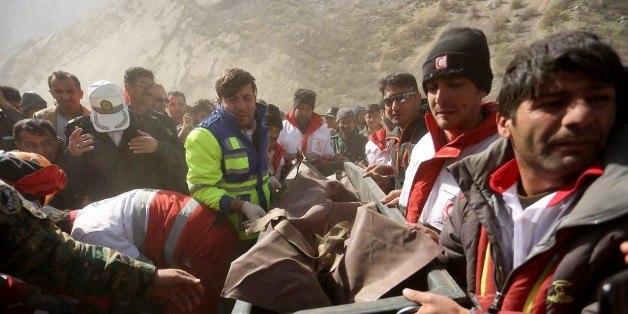 CHAHARMAHAL AND BAKHIARI, IRAN - MARCH 12: Rescue workers carry a body bag with a victim at the crash site of a private Turkish aircraft in Kiyar district of Chaharmahal and Bakhtiari Province of Iran on March 12, 2018. A private Turkish aircraft, with 11 people on board, crashed in southwestern Iran. Everyone on board reportedly died in the crash. (Photo by Ali Reza Motamedi/Anadolu Agency/Getty Images)