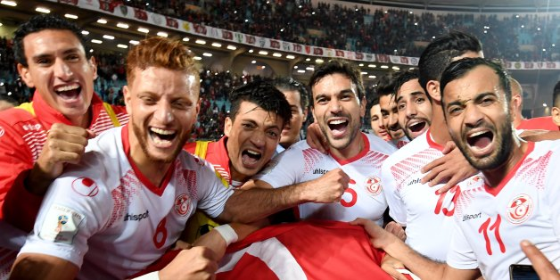 Players of the Tunisian national football team celebrate with their national flag after qualifying for the 2018 World Cup finals after drawing their qualifiers match against Libya at the Rades Olympic Stadium in the capital Tunis on November 11, 2017. / AFP PHOTO / FETHI BELAID        (Photo credit should read FETHI BELAID/AFP/Getty Images)