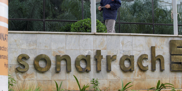 An employee stands near the headquarter  building of the state energy company Sonatrach in Algiers, Algeria june 26, 2016.Reuters/Ramzi Boudia