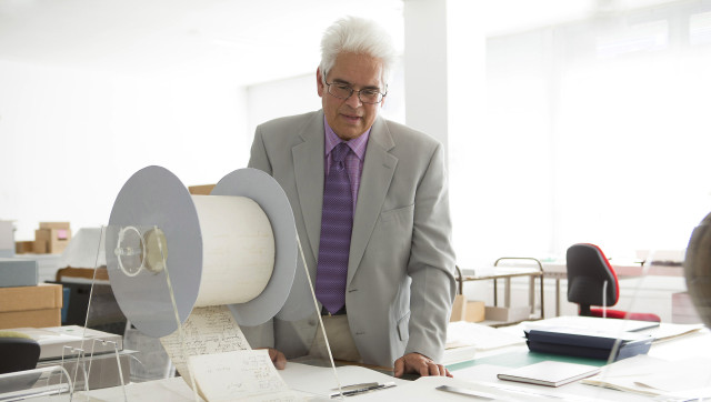 "In this handout photograph, author Ray Waru inspects files at New Zealand's national archives in Wellington following the release of his new book, ""Secrets and Treasures."" The book reveals information about rare historical gems buried in New Zealand's national archives, including a bizarre WWII plan to create a ""tsunami bomb"" and military X-Files detailing supposed UFO sightings. (AFP PHOTO / David Sanderson / manipula.co.nz)"