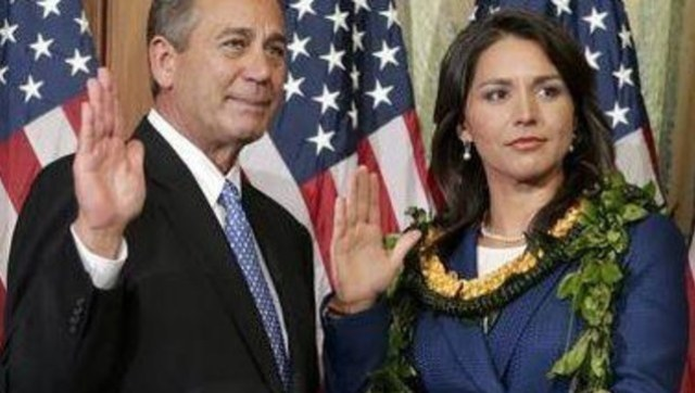 Rep. Tulsi Gabbard, the first Hindu in Congress, participates in a ceremonial swearing-in administered by Speaker of the House Rep. John Boehner.